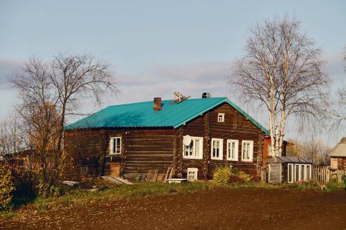 Värske akvamariinivärviline plekk-katus  eelmise sajandi esimesel poolel ehitatud elamul Kulömdini alevikus Komimaal.