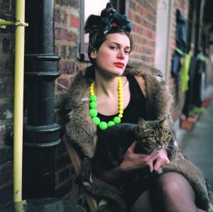 """Maria Kapajeva. Asja. Seeriast """"Kunstniku portree noore naisena"""", 2012. –2015. Autori loal.  Maria Kapajeva on Londonis elav Eesti vene rahvusest kunstnik, kes ise kirjeldab oma fotoseeriat: """"Enamik neist naistest ei ole kolinud uude riiki selleks, et seal abielluda, vaid et realiseerida oma loomingulist potentsiaali, ükskõik kas nad kirjutavad, joonistavad, maalivad, pildistavad või leiutavad."""""""