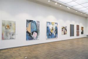 """Eesti noorte kunstnike tööd kipuvad olema sama dekoratiivsed nagu klassikutegi omad. Vaade Tallinna Kunstihoone suurde saalis, vasakul Liis Kogeri (1989) maal """"Lõputu lõik"""" (õli, lõuend, 2014), keskel on Liisa Jugapuu (1990) maalid """"Ma"""" (akrüül, lõuend 2015), ja paremal Sirje Peterseni (1959) maal """"Taeva all"""" (õli, lõuend, 2014)."""