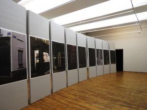 """Tartu Kunstimaja II korruse suures saalis oli Tarvo Hanno Varres valinud 22osalise fotoseeria """"Kättesaamatu mälestus (Brüsseli nurgad)"""" eksponeerimiseks üllatavalt mõjusa viisi: mastaapselt ruumi poolitanud kergelt kumerakaareline monoliitne sein tõkestas (või ka suunas) vaba ringiliikumist ja tuletas meelde mõnda teist olulist installatsiooni nagu Richard Serra dekonstrueeritud terasseina New Yorgis. Seina autor oli Neeme Külm. Kaire Nurk"""