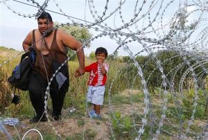 Põgenik koos lapsega Serbia ja Ungari vahelise okastraataia ääres.
