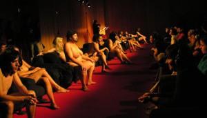 """Installatsioon-lavastuses """"sexyMF"""" on kaksteist esitajat alasti ja grimeeritud mõlemasooliseks: meeste nägudel on meik ja naistel habemed,  liigutused stereotüüpselt vastassoole omistatavad."""