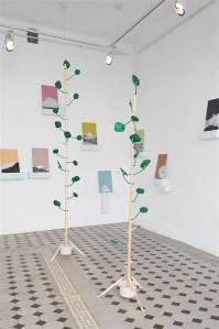 """Vaade Sigrid Viiru näitusele """"Hirmus ilus torukael"""". Draakoni galerii keskel seisab torulist peeglipuud meenutav installatsioon: roheliseks värvitud metall on kui tüvi ja tagasivaatepeeglid näivad lehtedena."""