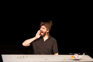 """Iisraeli nukukunstniku Ariel Doroni lavastuse """"Plastikkangelased"""" minimalistlik lava: üks mees, laud ja naiivsed mänguasjad."""