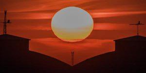 Päike koos Merkuuriga (Päikese ketta allservas) loojumas vesilennukite angaaride taha.