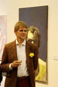 """Margus Punab näituse """"Maskuliinne eksistentsialism"""" avamisel Nooruse galeriis. Taustal on Jaan Toomiku maali """"Valmisolek"""" (2007)."""