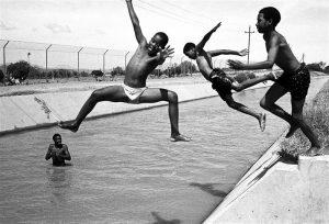 Juhan Kuus. Esimene koolipäev ja 33 kraadi sooja. Bridgtoni linnakese lapsed jahutavad end kuivenduskraavis tapamaja lähistel.  Lõuna-Aafrika, 8. XII 2003.